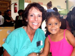 Judy Gura, RN, with a child in a La Romana orphanage. Photo by Brenda Bazyluk.